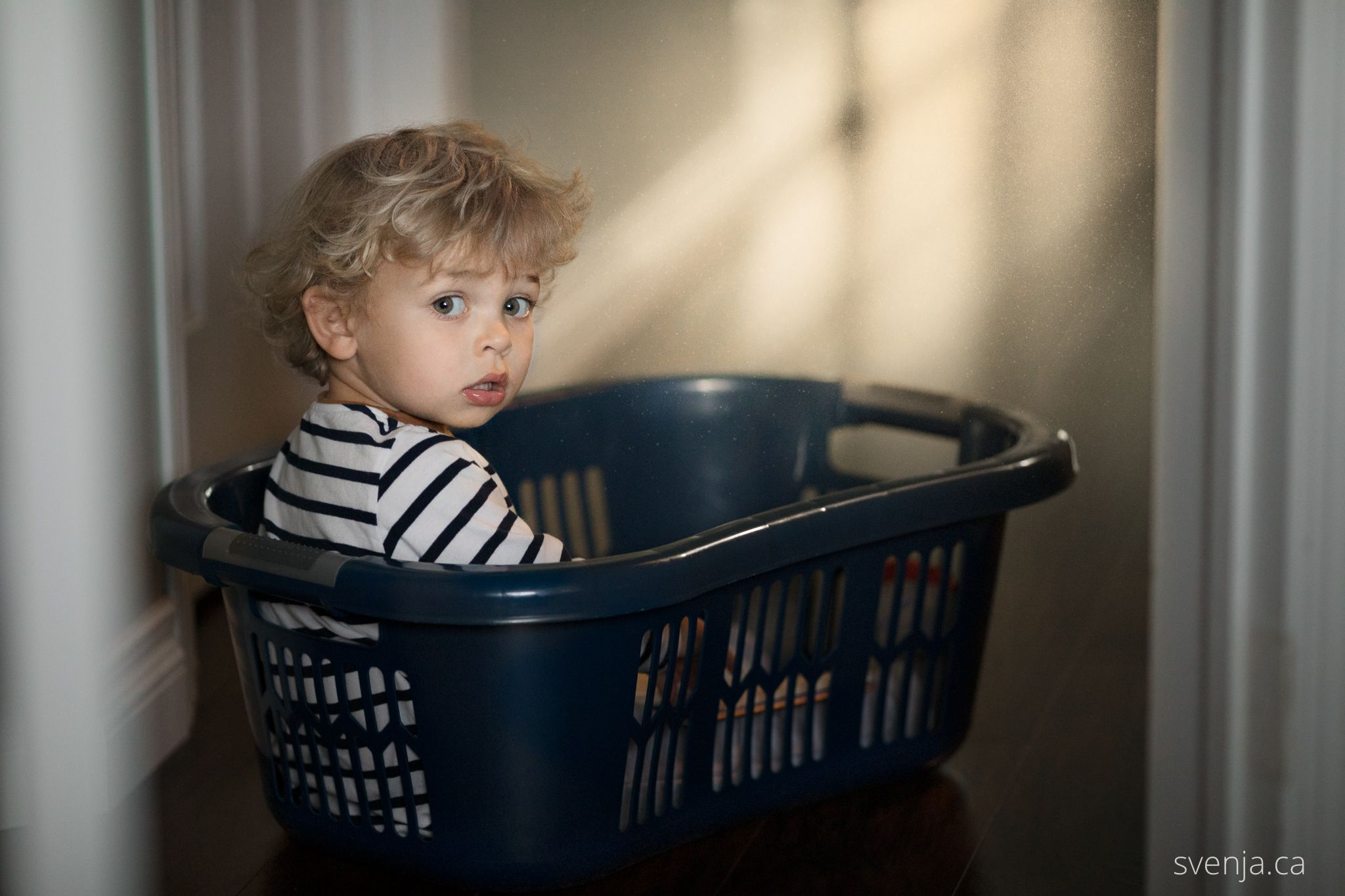 a boy sites in a clothes basket