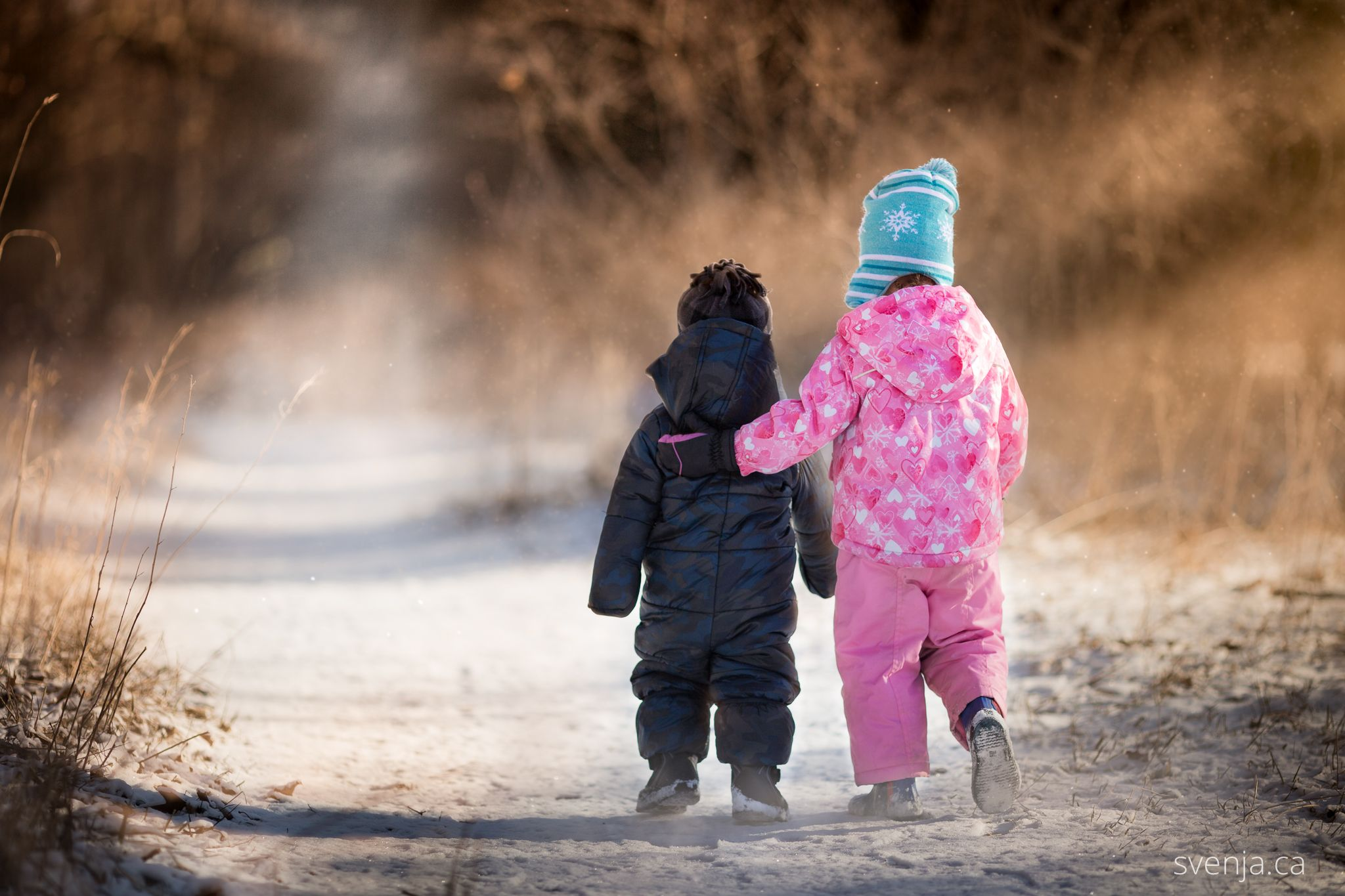 boy and girl in snowsuits walk down a path