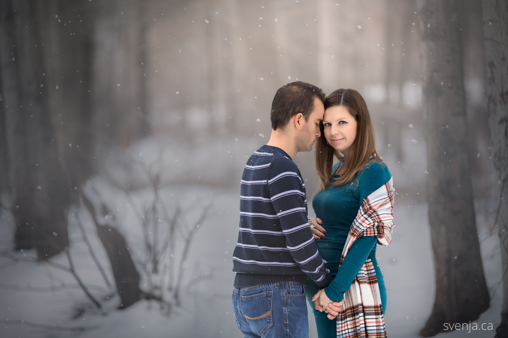 maternity photo of wife and husband in the forest with snow