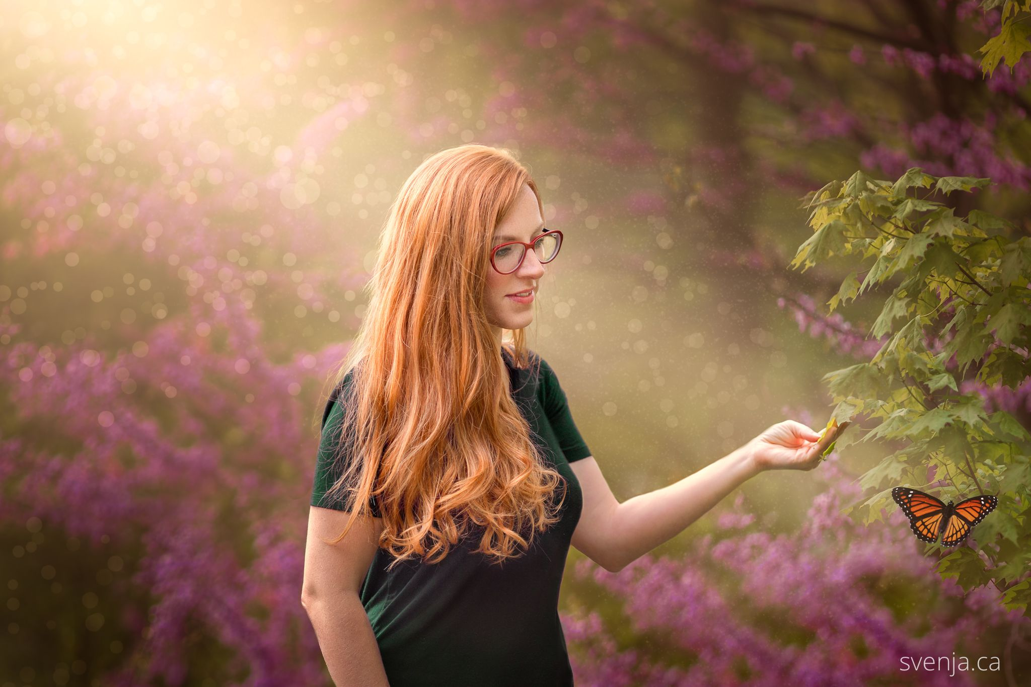 red haired woman looking at a butterfly