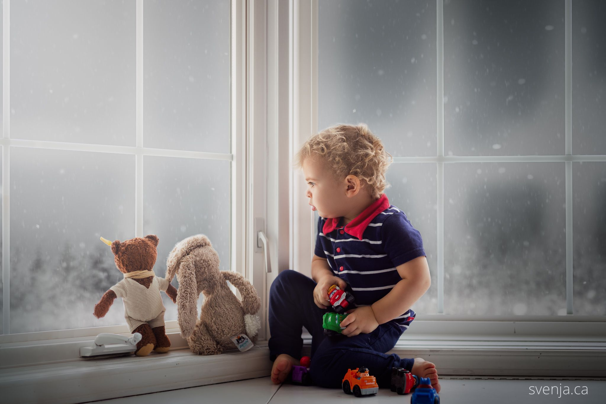 a toddler boy sits with his stuffed animals in a bay window looking at snow