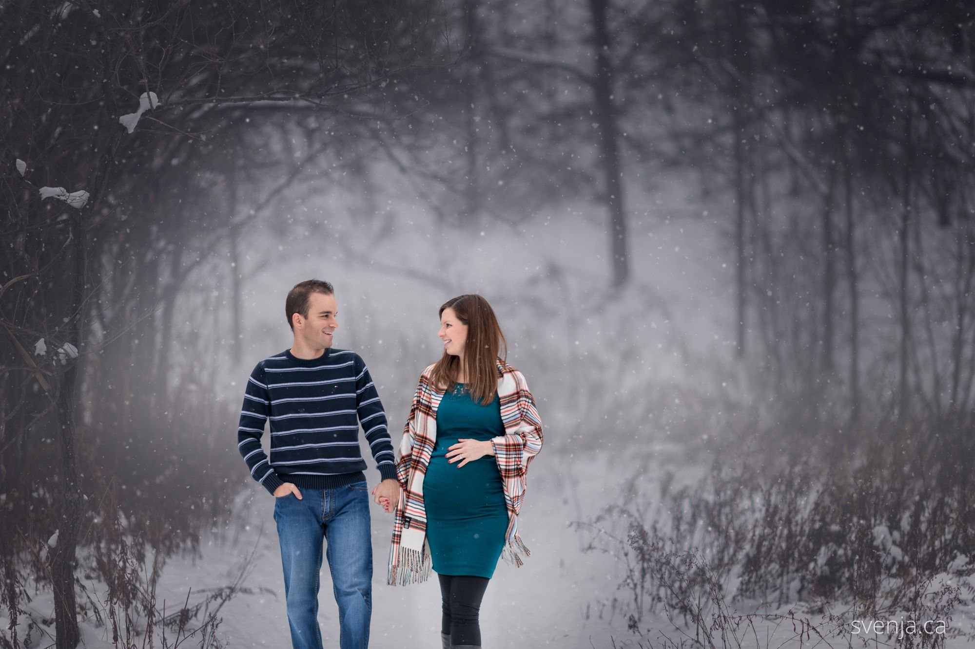 an expecting couple walked together through a snowy forest