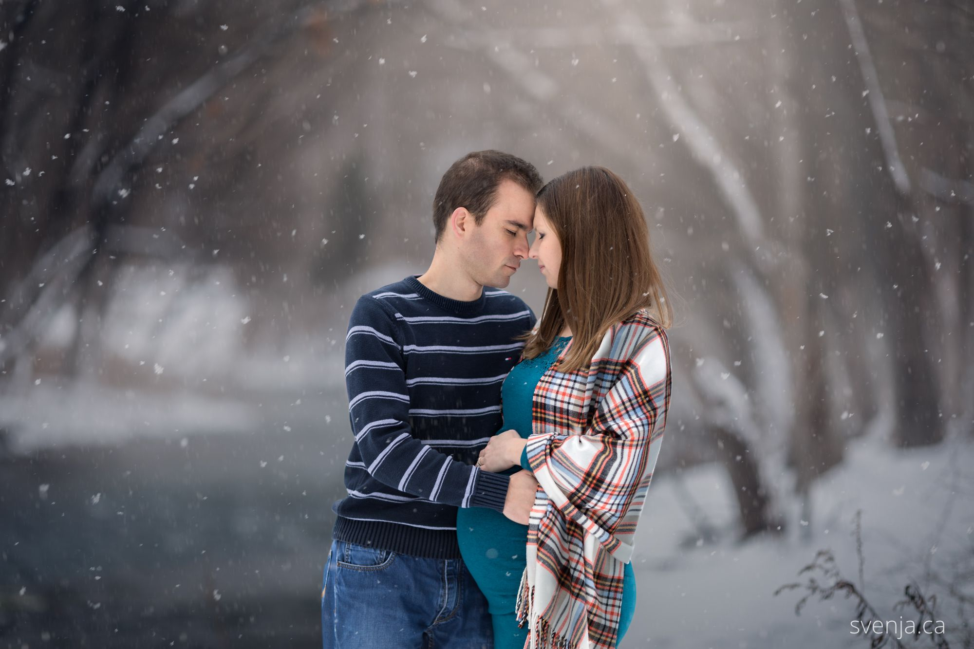 expecting mother and her husband embrace closely with eyes closed with a snowy background