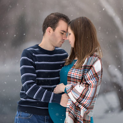 thumbnail photo of maternity session with couple embracing closely in a snowy forest.
