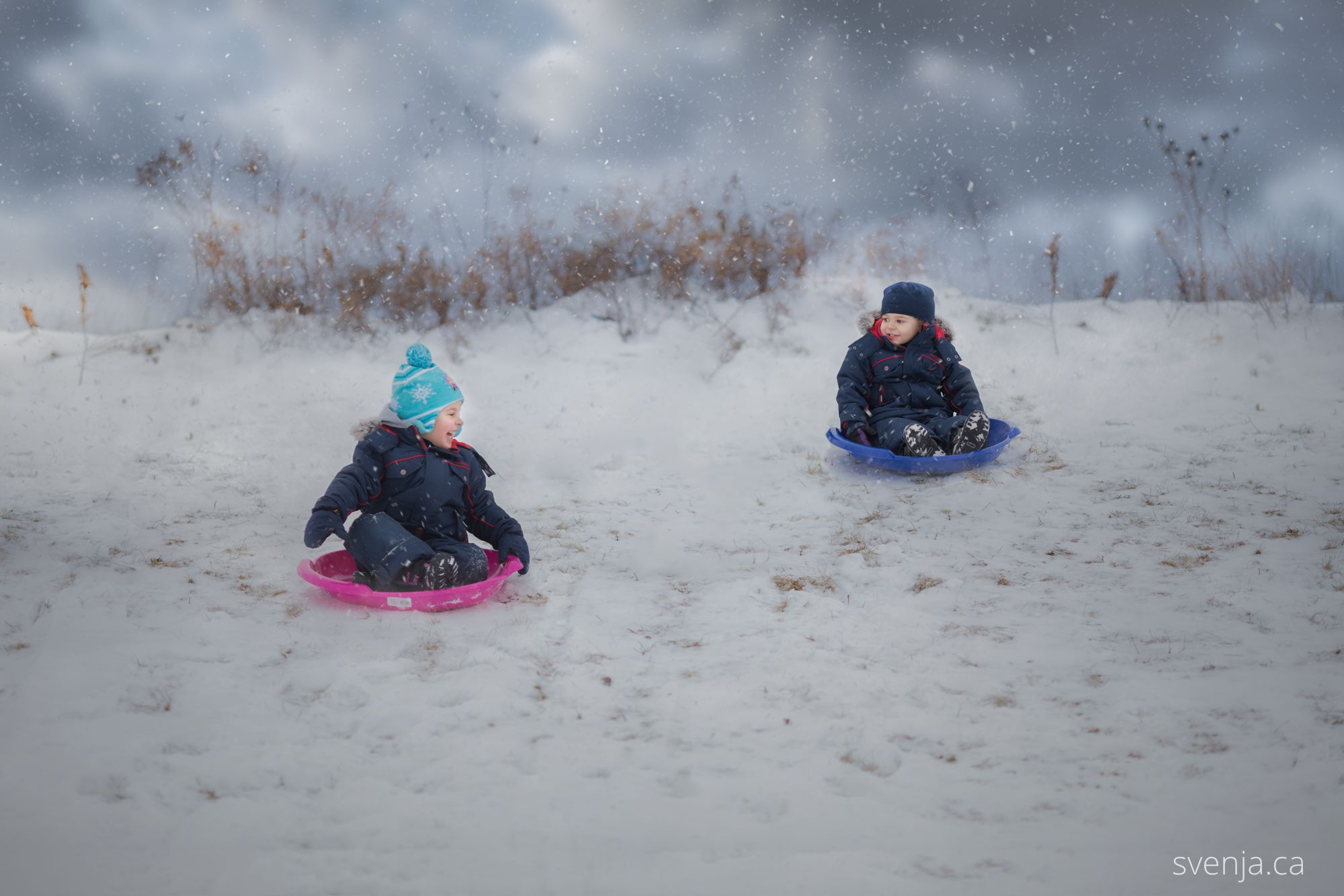 mother prepares her two children for sledding down a hill