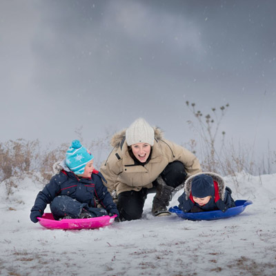 mother smiling as children go down a hill on their sleds