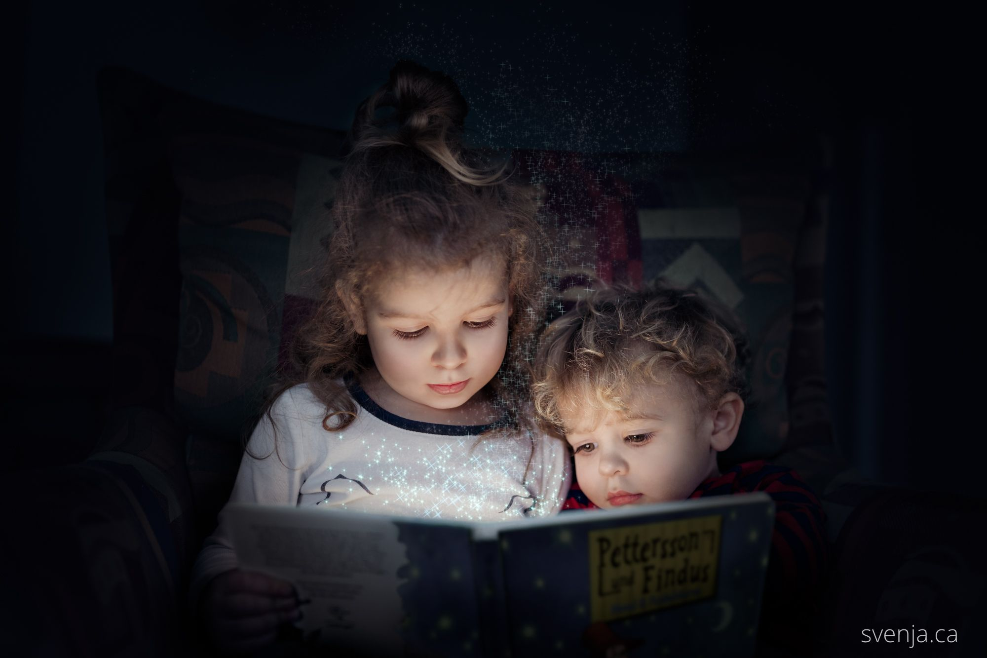 two young children sit on a chair and read a book together