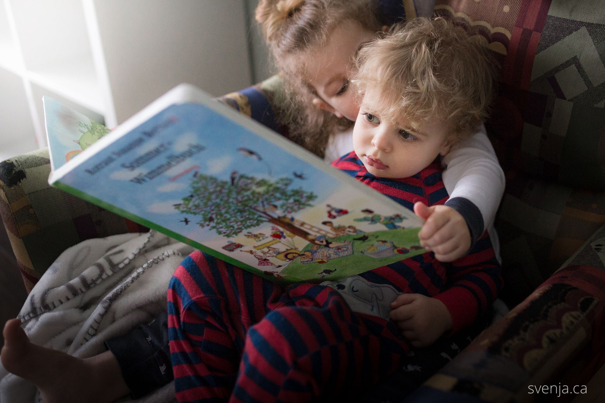a big sister holds her little brother while reading a book