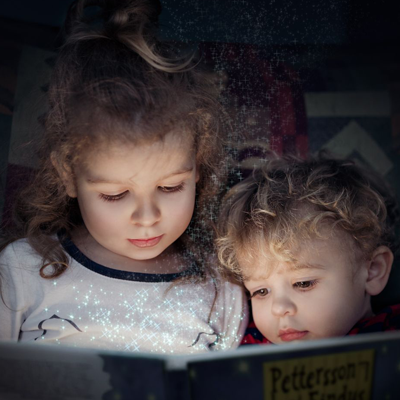 two children sit in the dark reading a book
