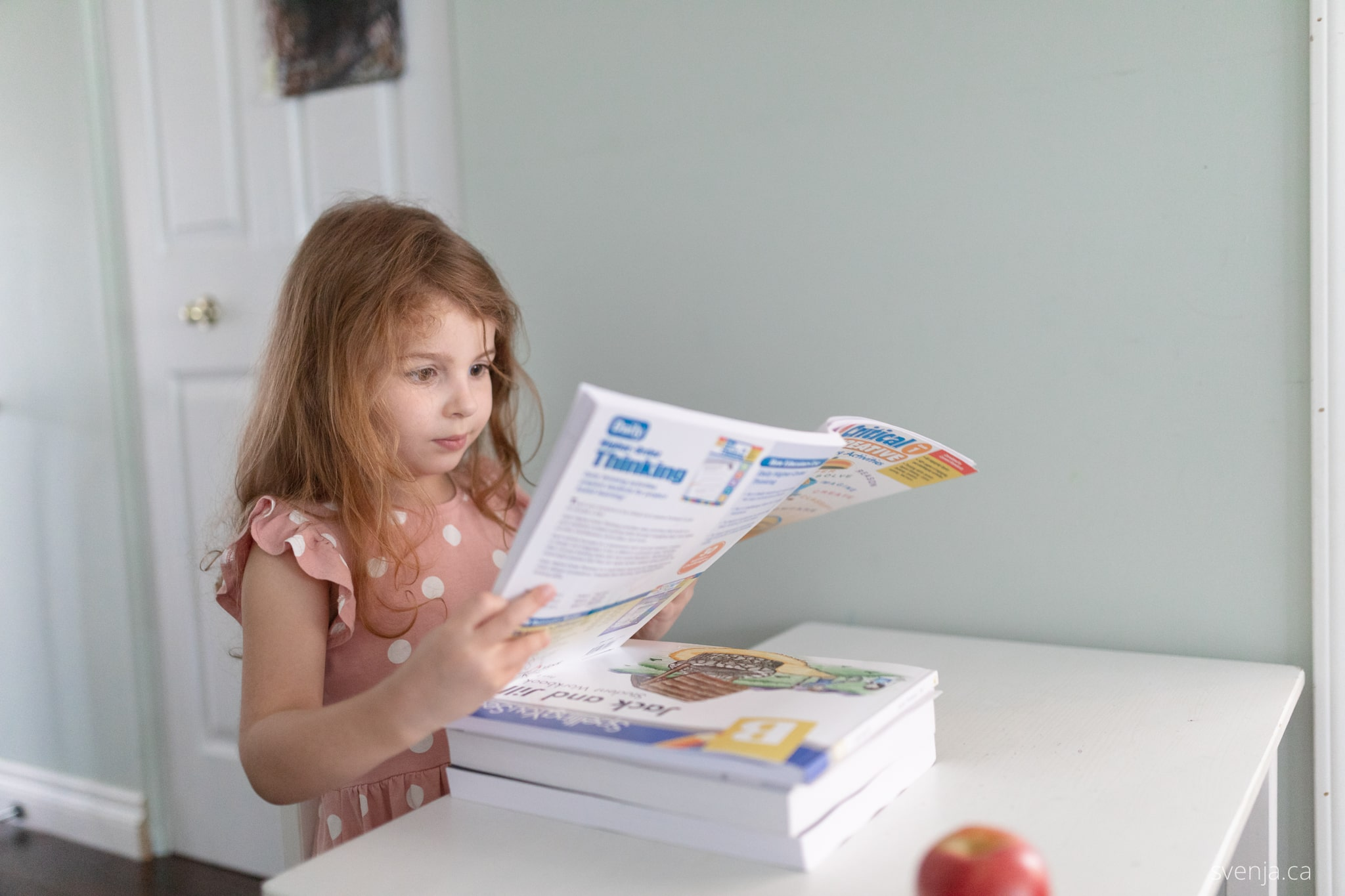 a young girl looks over a work book while seated at a desk