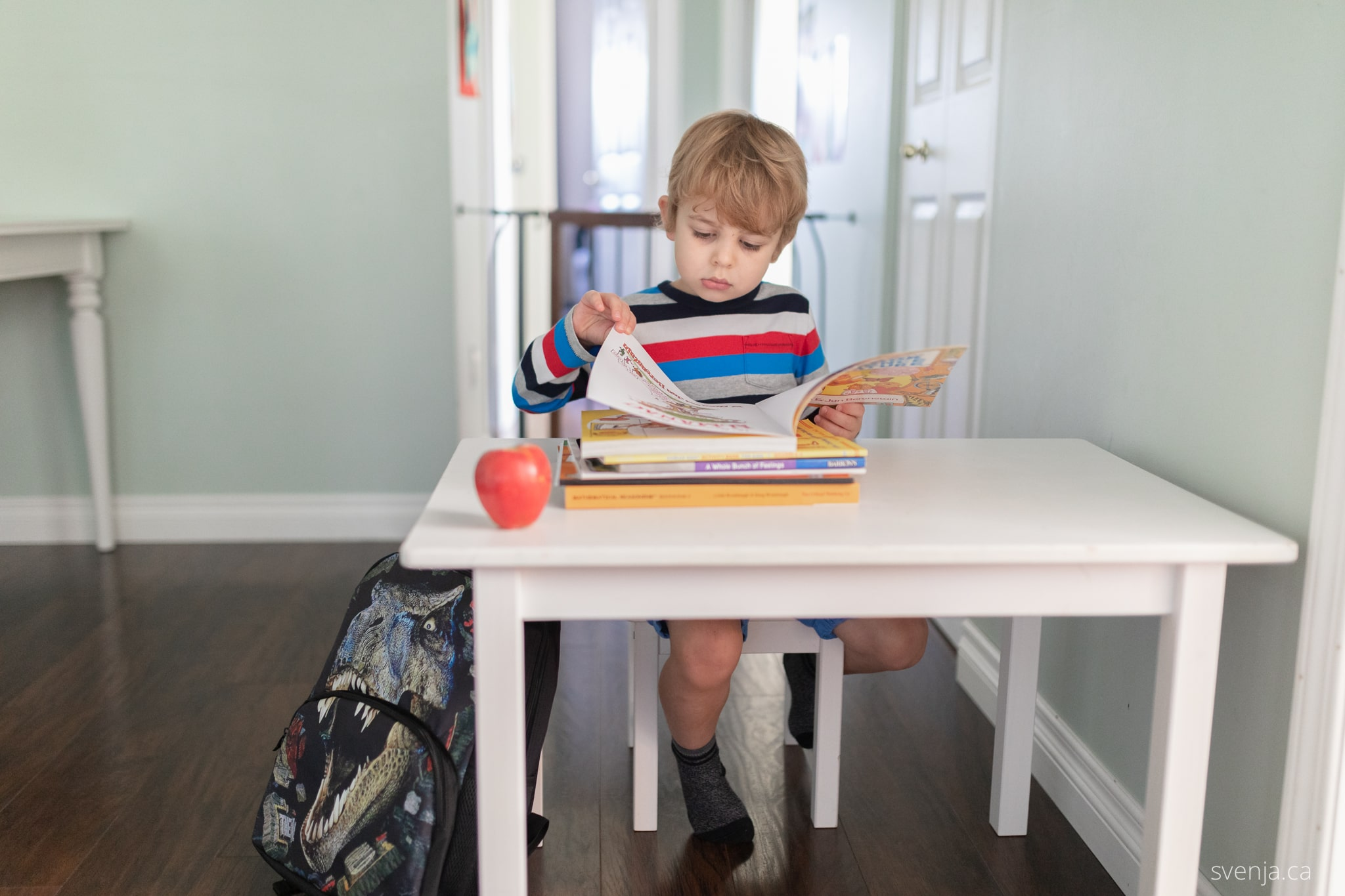 a young boy looks over a work book while seated at a desk