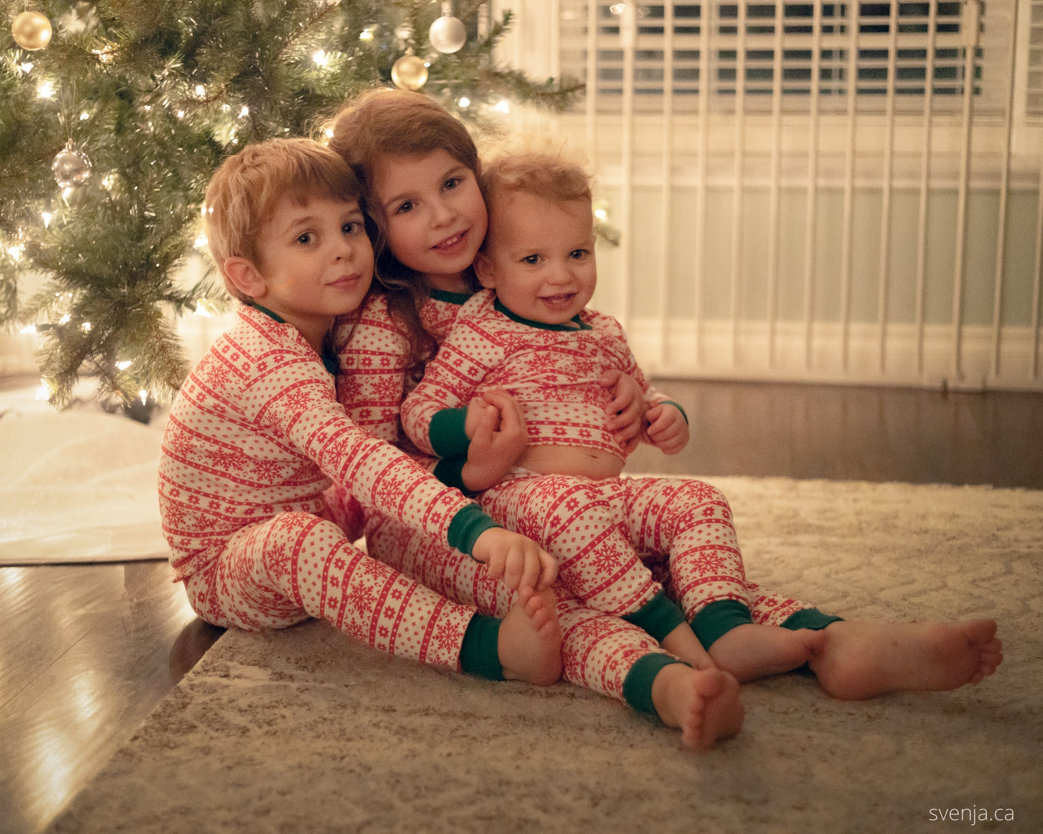3 children in matching pajamas sit in front of a Christmas tree