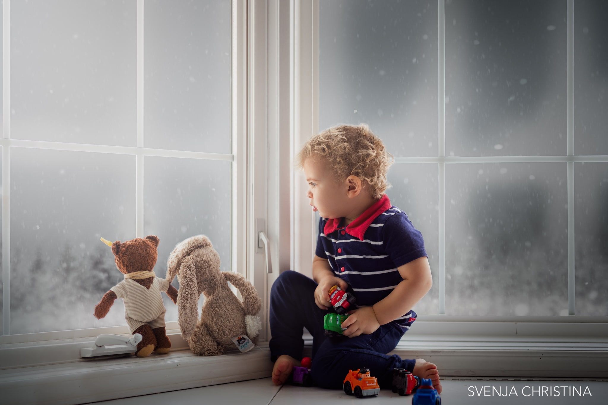 young boy looks outside a window at snow with 2 teddy bears with him