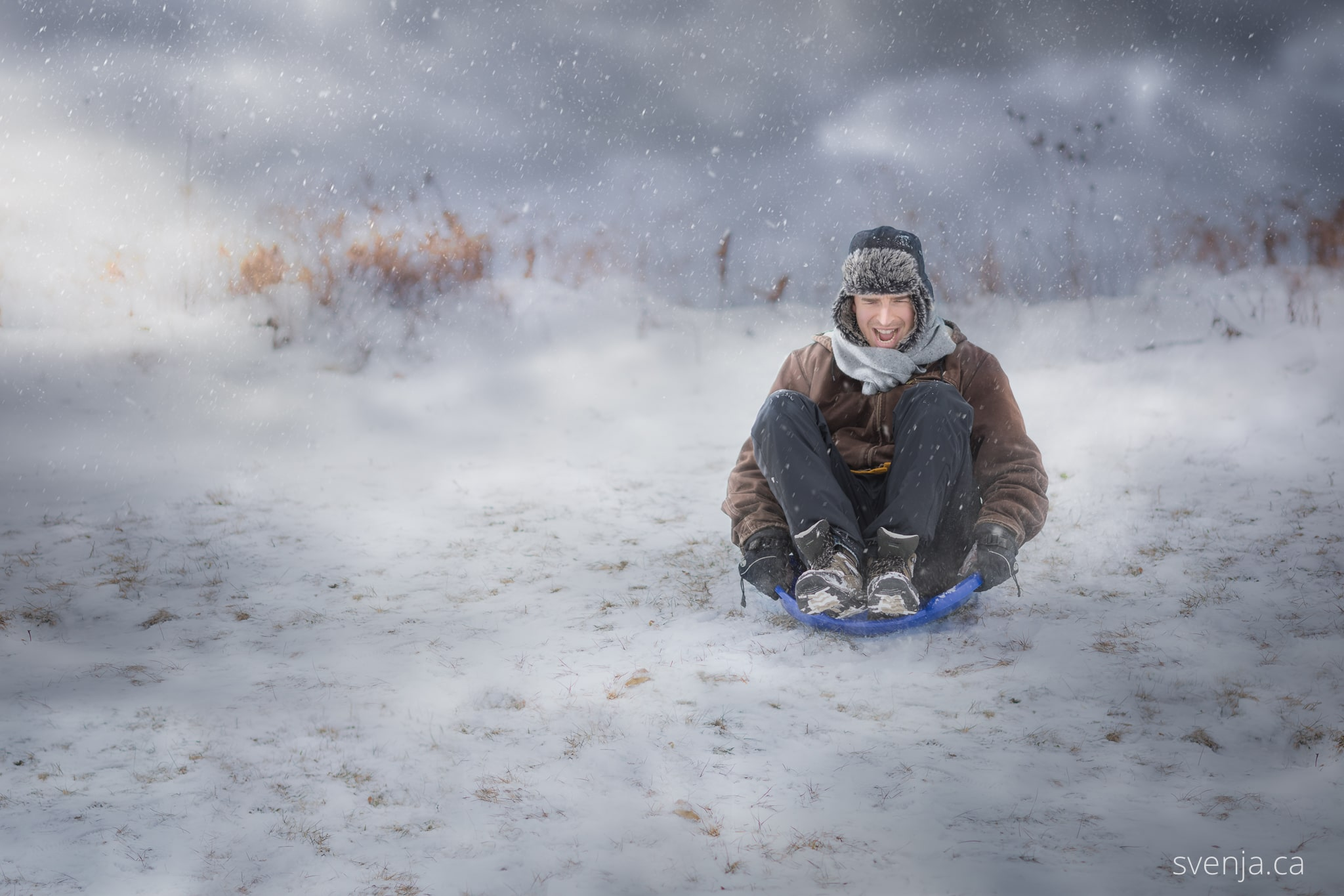 foolish man slides down a snowy hill in a child's toy