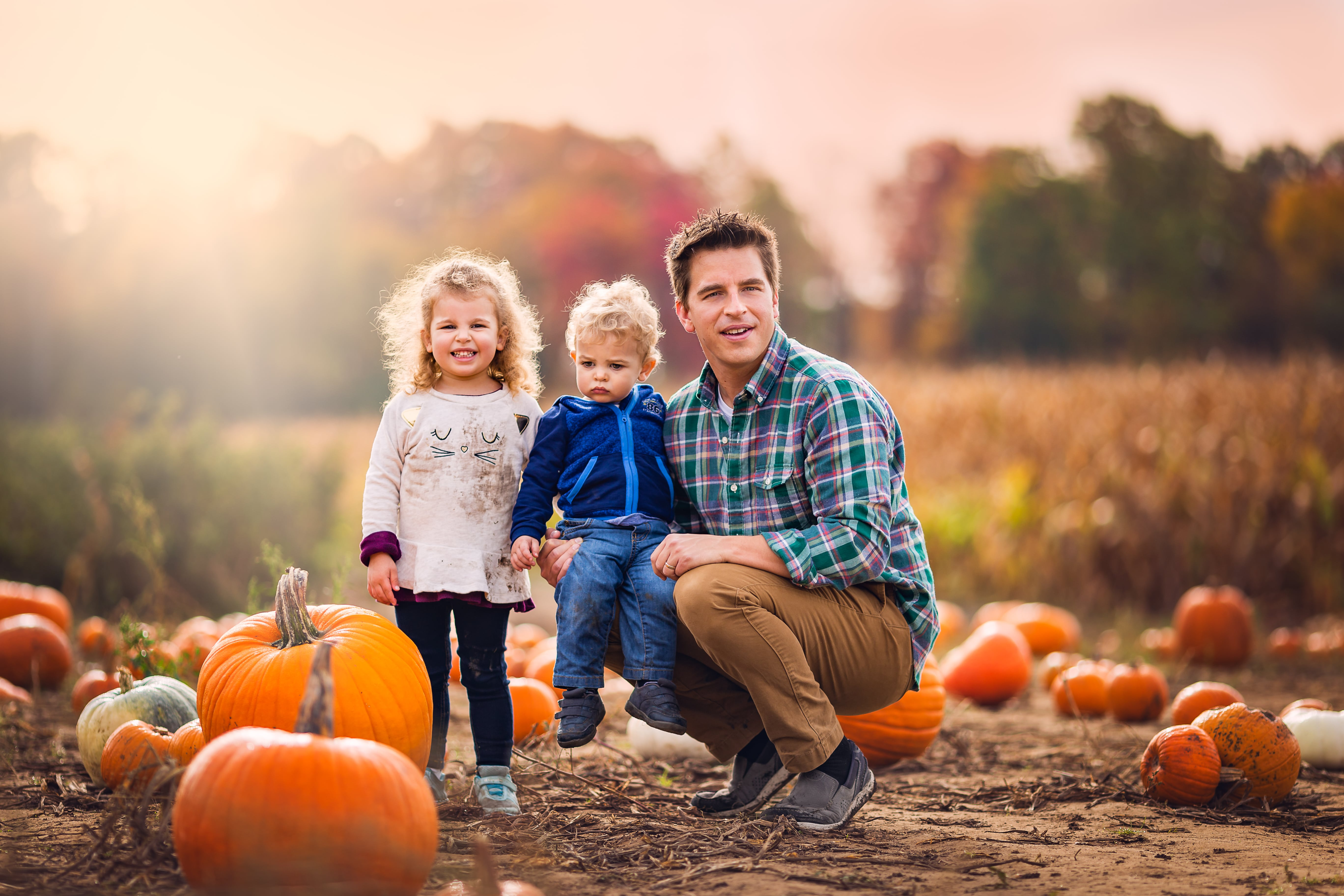 father and two children in a pumpkin patch