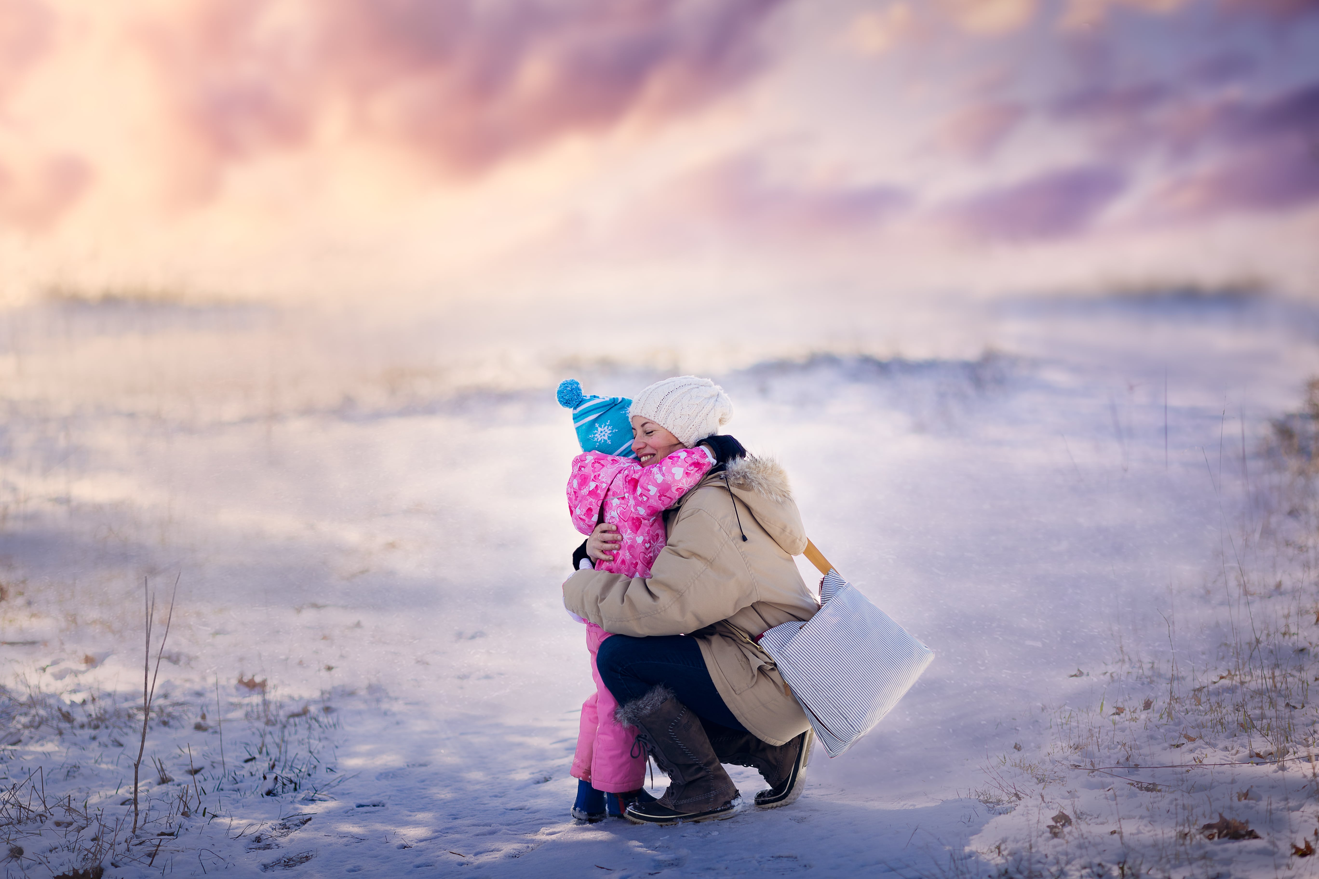 mother and daughter embrace in a snowy outdoor scene