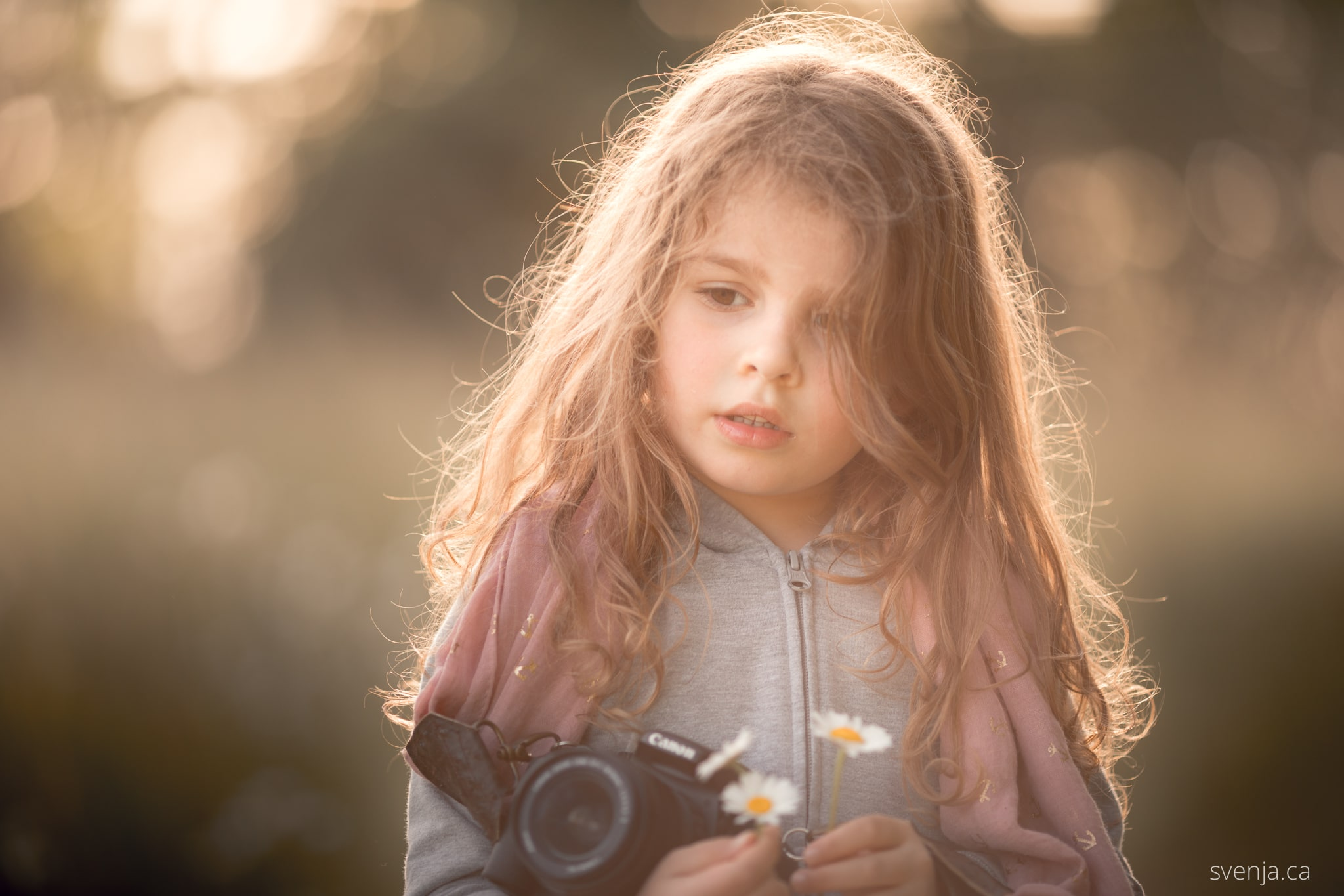 young girl holds a camera outside
