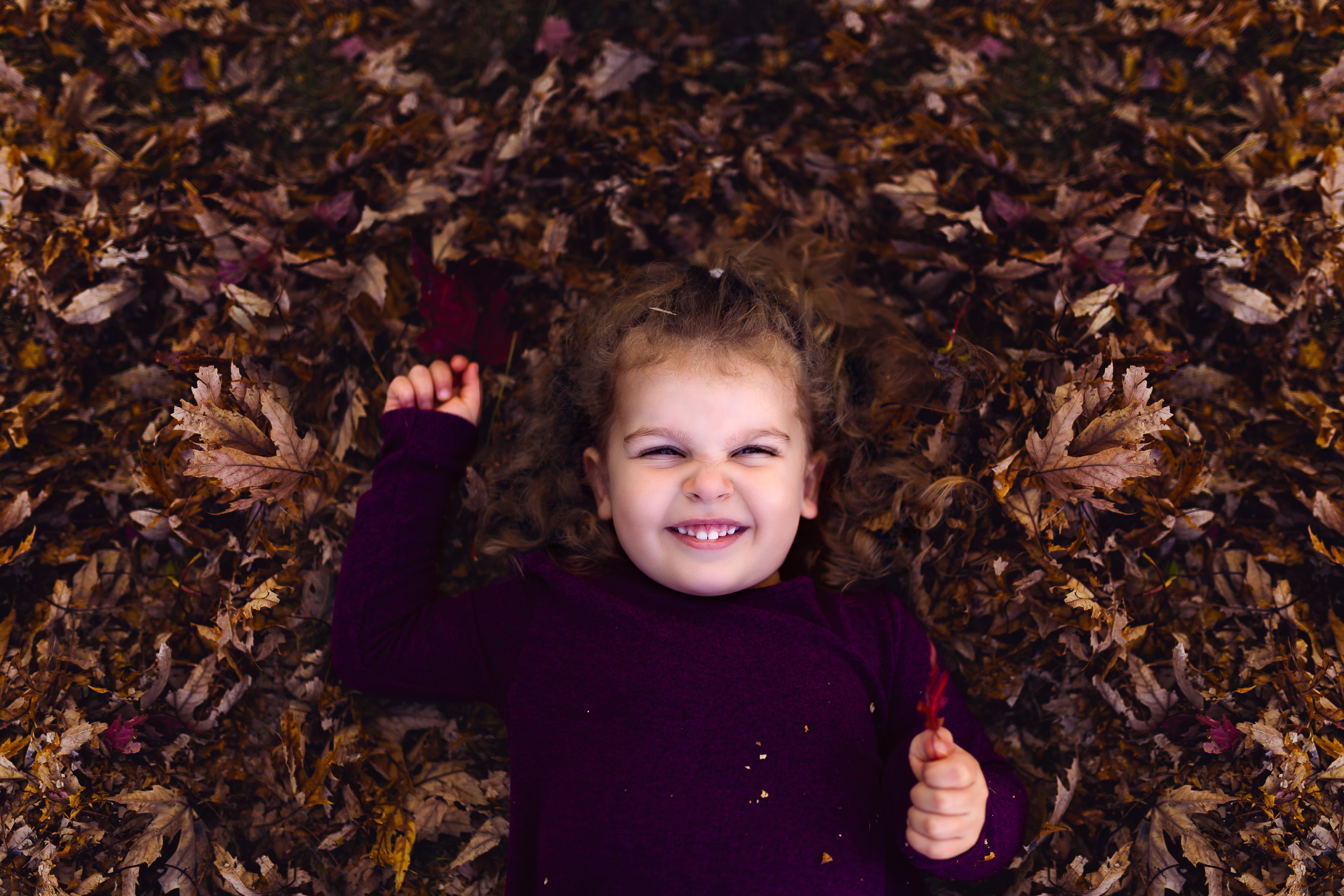 little girl lays in leaves in autumn
