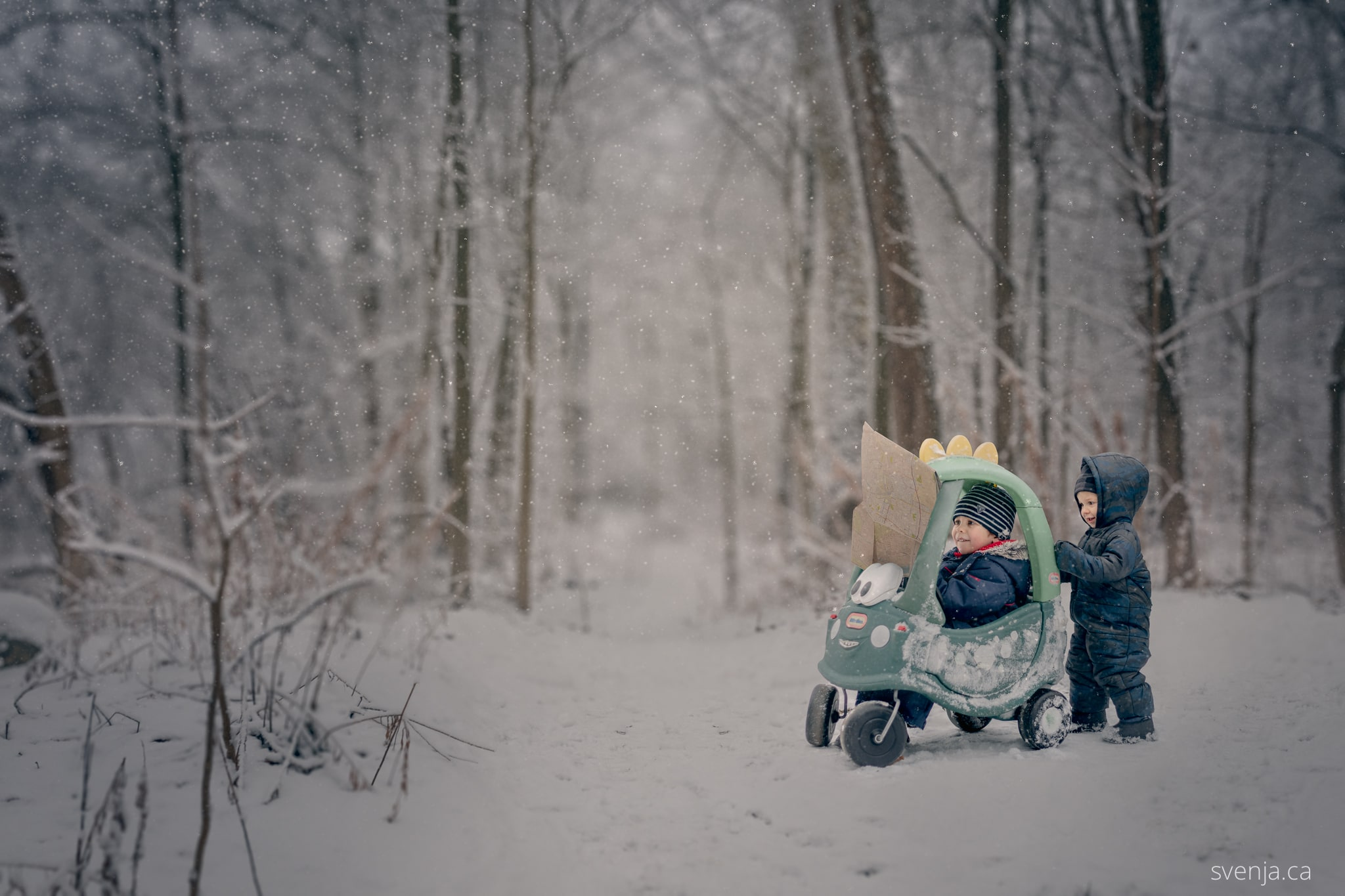 two young boys outside in forest, one sitting in child's toy car, both looking at a map