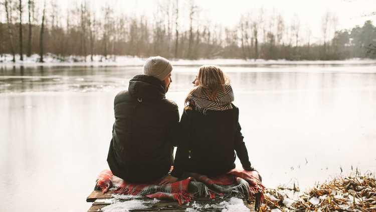 Paar zittend aan de oever van het meer