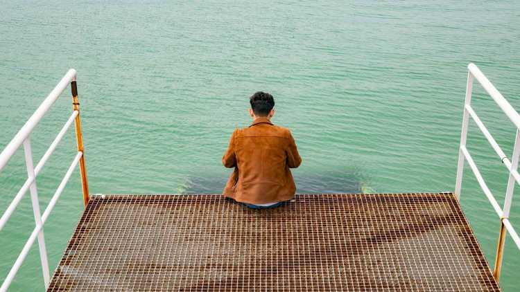 foto van jongen zittend aan de haven