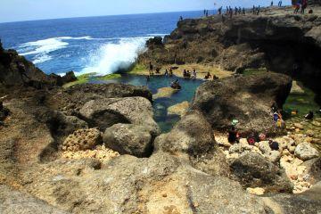 Pengunjung nekat bermain air di sekitar kolam air asin yang terbentuk alami di sepanjang pesisir Pantai Kedung Tumpang, Tulungagung, Jawa Timur, Minggu (29/11).