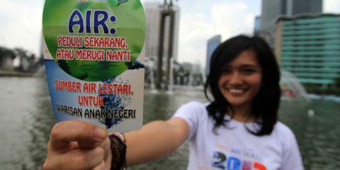 Seorang aktivis menunjukan stiker air warisan anak negeri ketika kampanye Hari Air Sedunia di kawasan Bundaran Hotel Indonesia, Jakarta, Jumat (22/3)