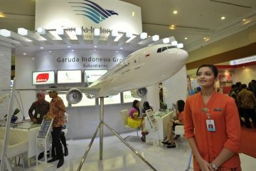 Petugas PT Garuda Indonesia mengamati replika pesawat Boeing 777-300ER saat Pameran Inovasi BUMN, Jakarta, Kamis (27/6).