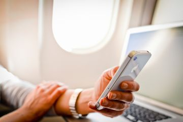 Woman using iPhone 4s and laptop in airplane during flight