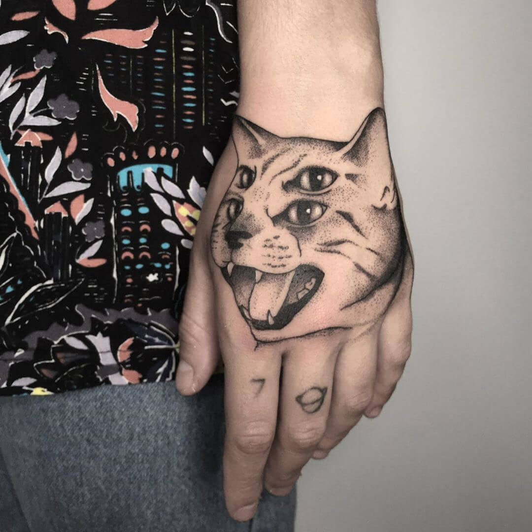 Double eyed cat tattoo on the hand by Filipa Vargas