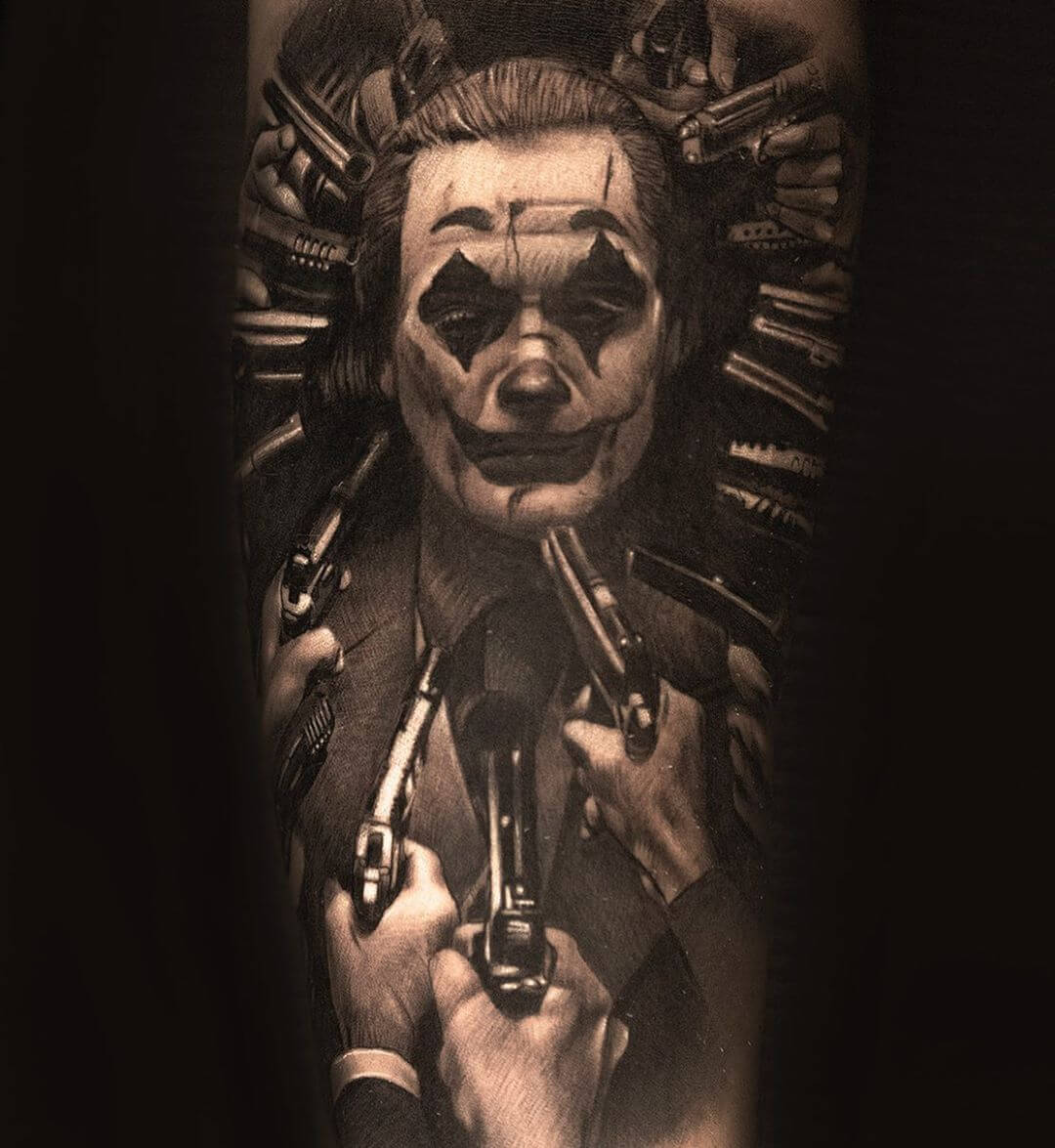 Tattoo of Joaquin Phoenix as the joker surrounded with guns to his head