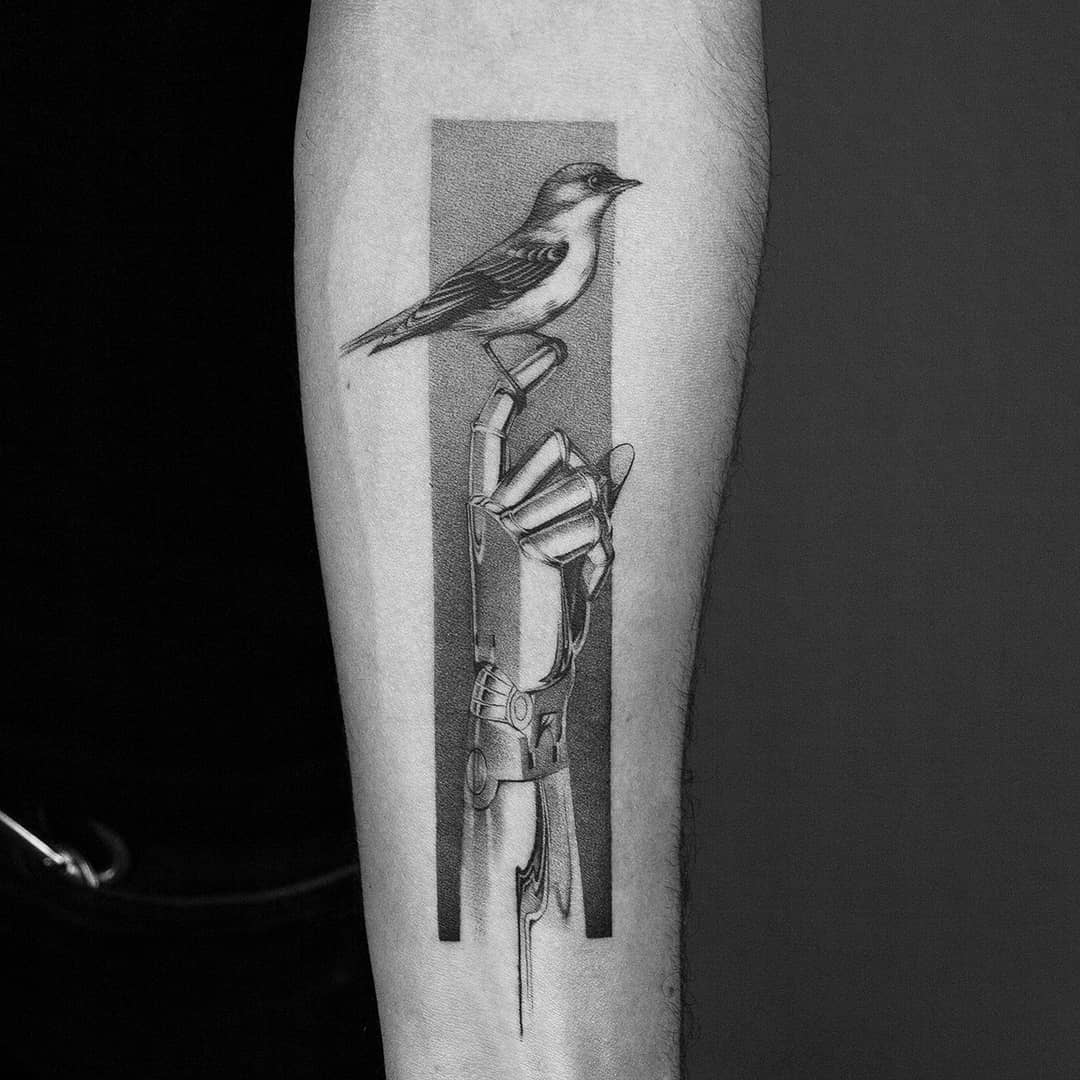 Bird sitting on robot hand tattoo by Amanda Piejak