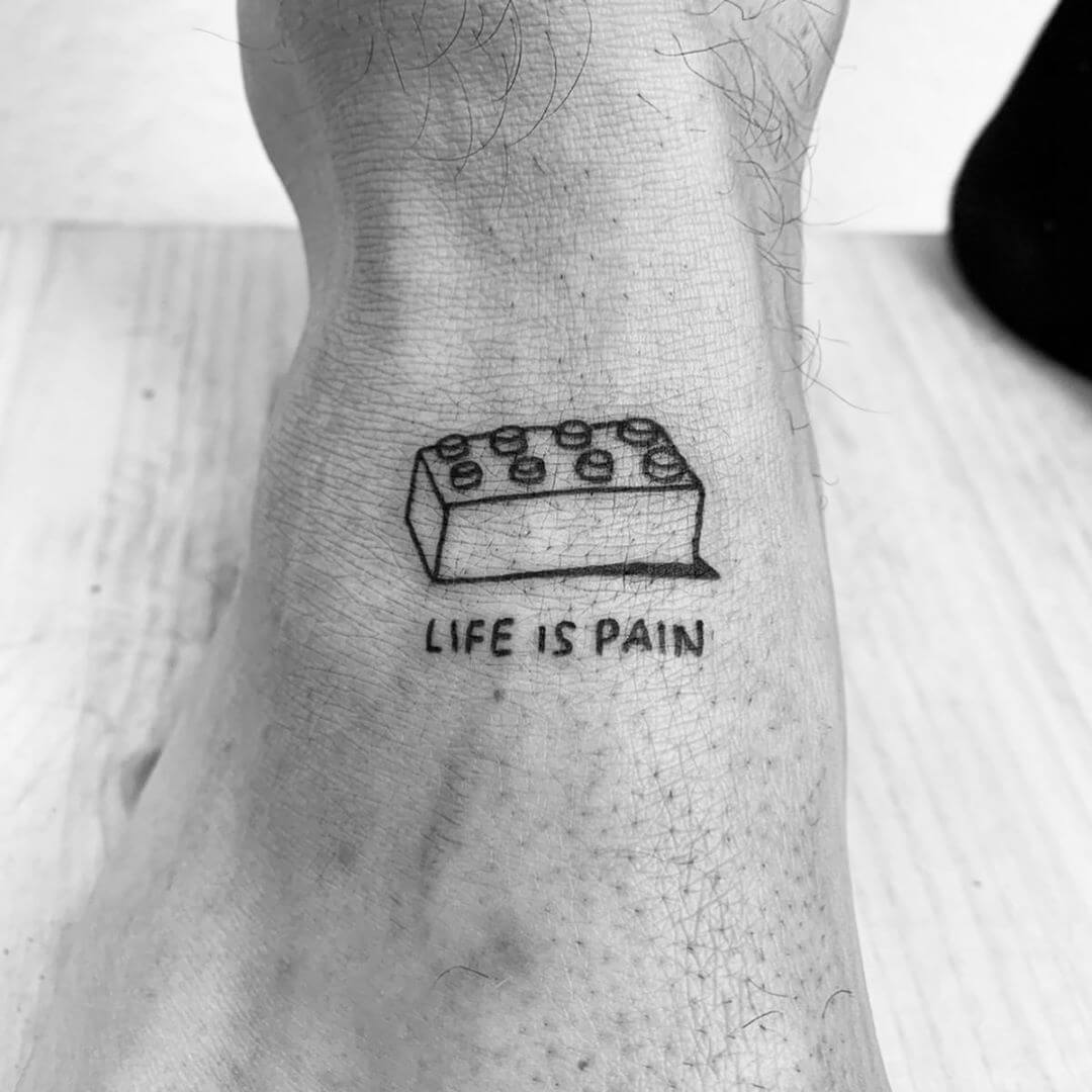 Lego brick tattoo with the text 'Life is pain' by Escozcc