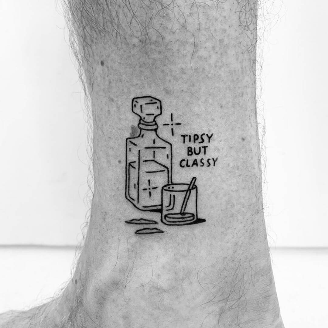 Stil life tattoo of drink with the text 'Tipsy byt classy' by Escozcc