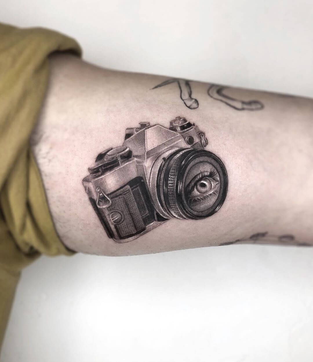Dotwork tattoo by Maya Gat of an eye in a camera lens