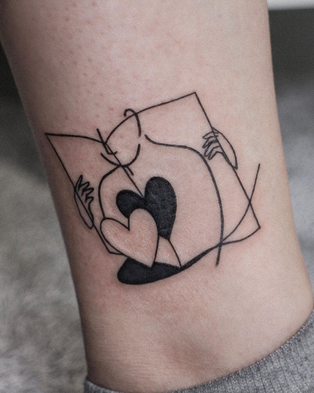Illustrative tattoo of a man reading a book with his heart by Minigreemer