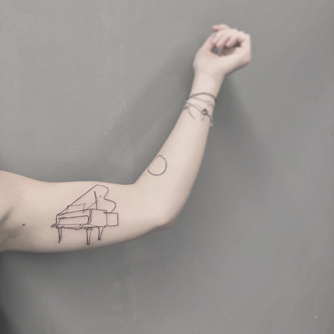 Oneline tattoo of a piano