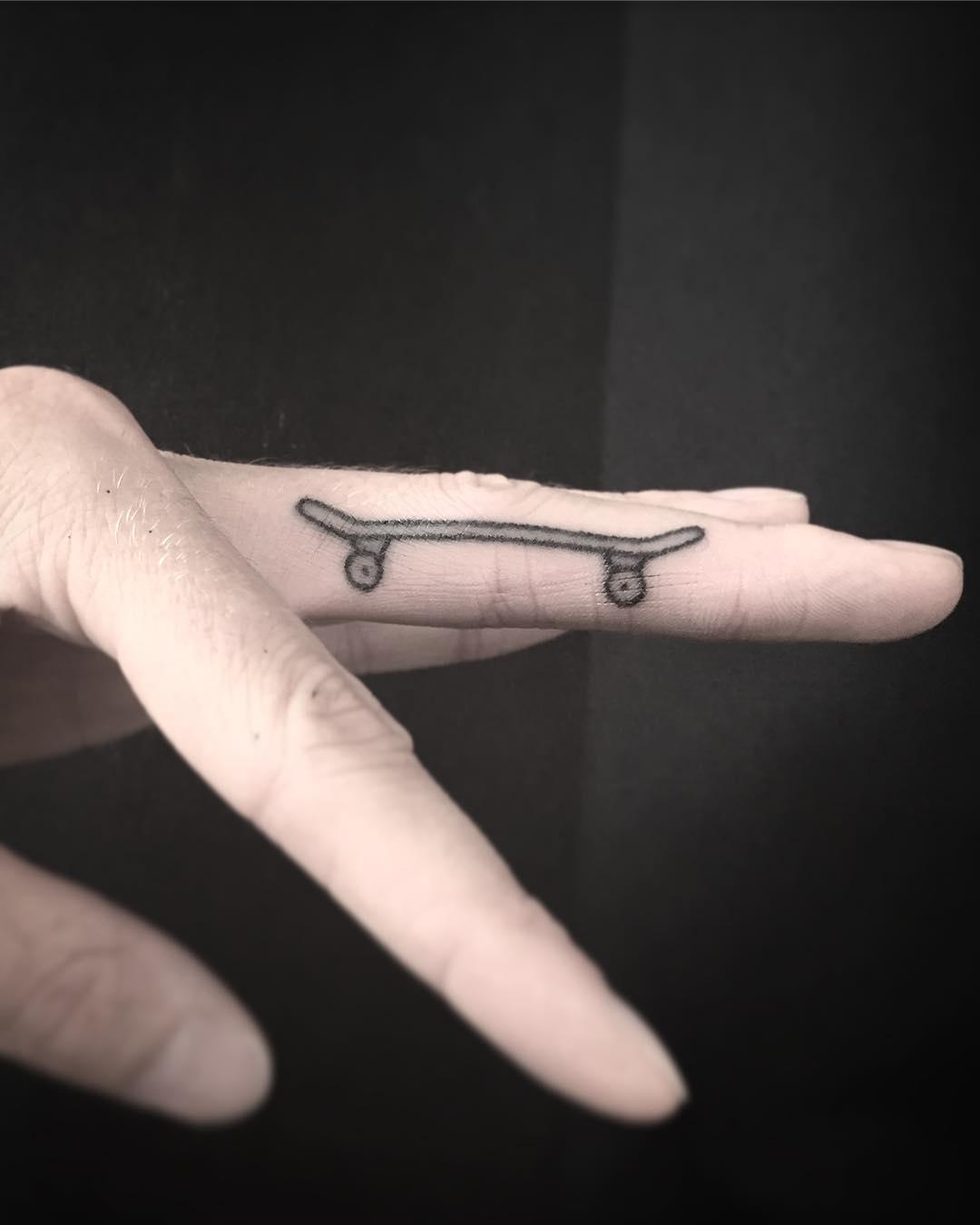 Little skateboard tattooed on a finger