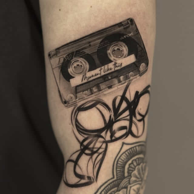 Casette tape with the title 'a moment like this', tattoo by tdantattoo