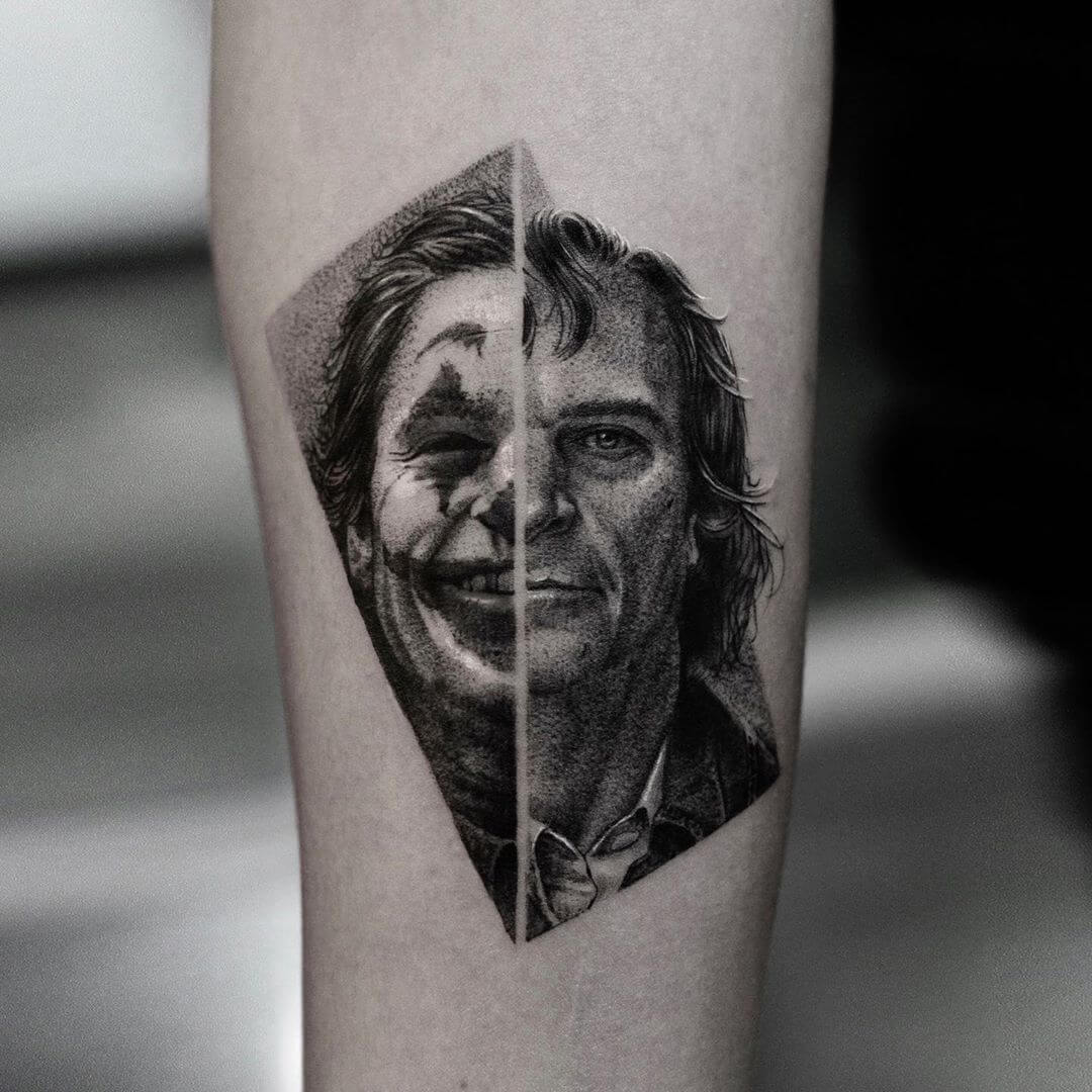 Tattoo portrait of Joaquin Phoenix where half his face is him and half his face it painted like The Joker
