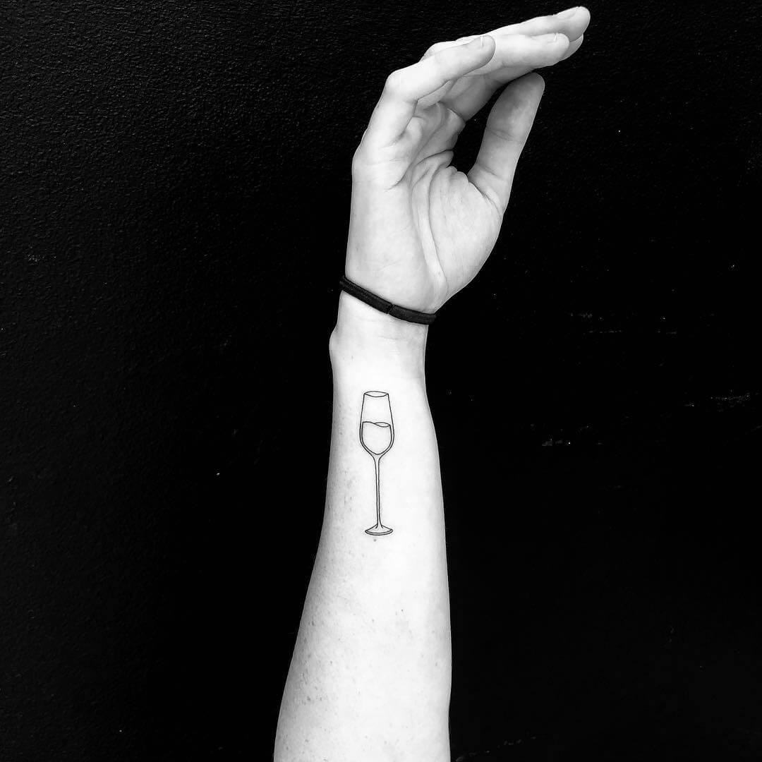 Glass of wine on arm minimal tattoo