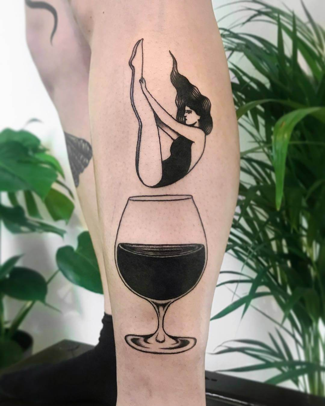 Woman falling in wine tattoo