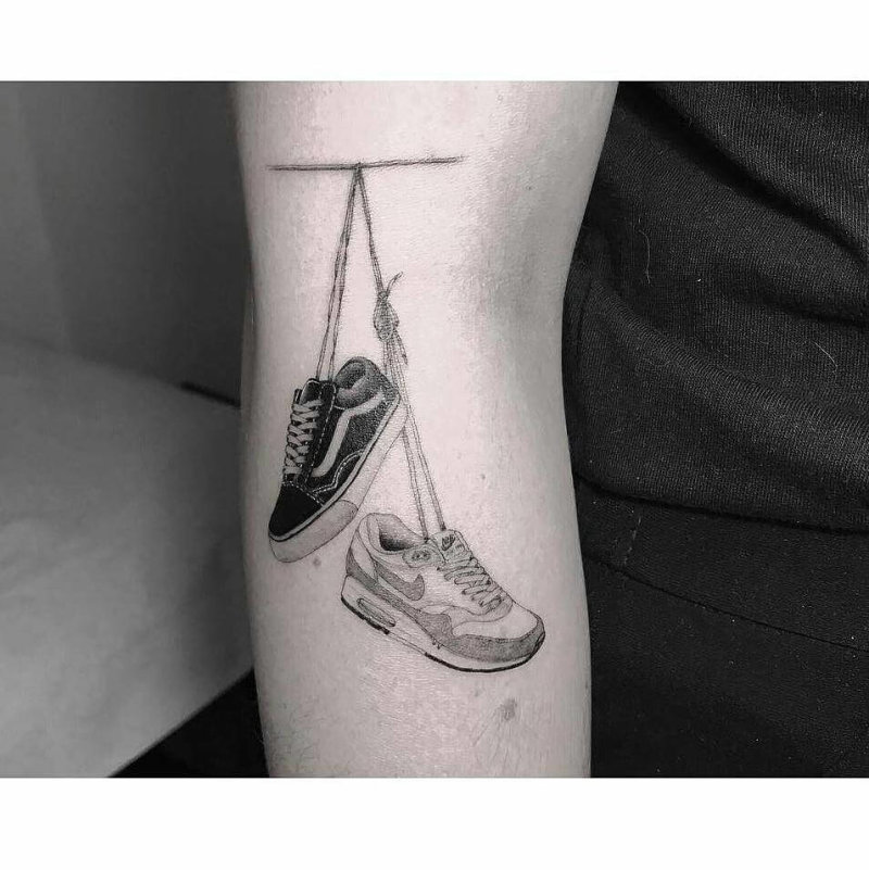 Two sneakers handing by their laces tattooed on the arm