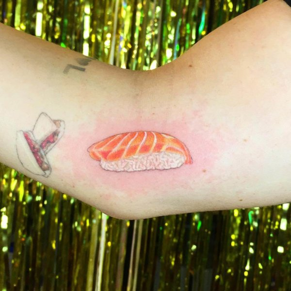 Realistic tattoo of a piece of salmon sushi