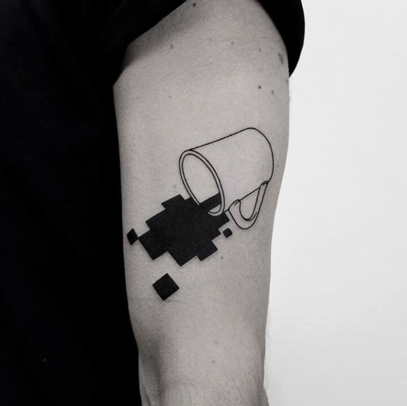 Tattoo of a coffee mug with pixelated coffee falling out