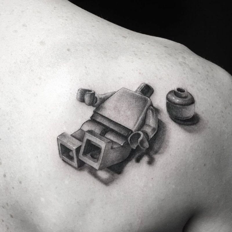 Lego figure with his head next to him tattoo