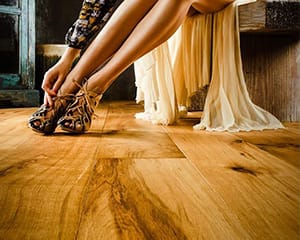 woman taking shoes off on signature bespoke wood flooring