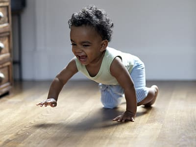 baby crawling on a solid wooden floor