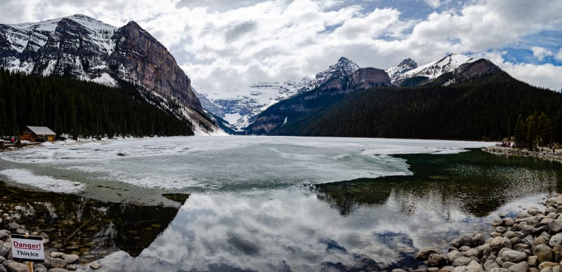 lake louise covered in ice under cloudy skies