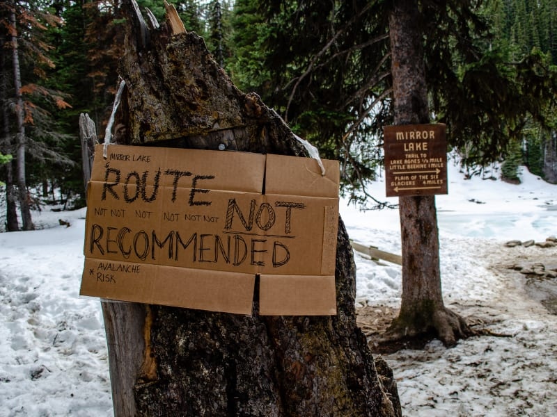 a warning sign written on cardboard indicating travel not advised beyond that point due to avalanche risk